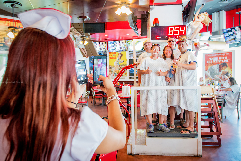"""The Heart Attack Grill gladly serves up the infamous Octuple Bypass Cheeseburger with extra mayo and bacon. The hospital themed restaurant has become famous for putting the spotlight on unhealthy fastfood by serving and promoting the most obnoxious versions of the same. """"Patients"""" weighing more than 350 pound eat for free, and nurses will spank you if you can't finish your meal. The eight layered cheeseburger with mayo and bacon packs about 20.000 calories."""