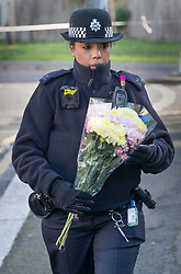 © Licensed to London News Pictures. 07/03/2019. London, UK. A police officer carries a floral tribute, brought by a member of the public,  to the crime scene in North Birkbeck Road in Leyton in east London where a murder investigation has been launched after a man in his twenties was stabbed on Wednesday. Photo credit: Peter Macdiarmid/LNP