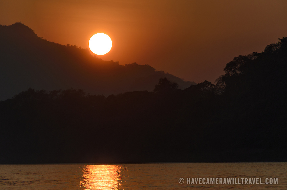 Just moments before the sun disappears behind a mountain on the horizon at sunset on the Mekong River near Luang Prabang, Laos.