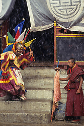 Asia, Nepal, Himalayas, Solu Khumbu region. Buddhist monks perform masked dance at Mani-Rimdu festival during snowstorm, Tengboche Monastery.