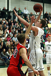 10 January 2015:  Trevor Seibring blocks out the blocking arm of Ryan Kase to get off his shot during an NCAA mens division 3 CCIW basketball game between the Carthage Reds and the Illinois Wesleyan Titans in Shirk Center, Bloomington IL