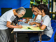 07 AUGUST 2016 - BANGKOK, THAILAND: A Thai woman signs in to pick up her ballot at polling place at Wat That Thong in Bangkok. Thais voted Sunday in the referendum to approve a new charter (constitution) for Thailand. The new charter was written by a government appointed panel after the military coup that deposed the elected civilian government in May, 2014. The charter referendum is the first country wide election since the coup.      PHOTO BY JACK KURTZ