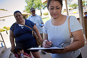 20 JUNE 2009 - PHOENIX, AZ: A woman signs in at the walk in clinic at the Cultural Cup. The walk in clinic at the Cultural Cup Food Bank started two years ago when Cultural Cup founder Zarinah Awad wanted to expand the food bank's outreach and provide basic medical care for the people who use the food bank. The clinic sees, on average, 7 - 11 patients a week. Awad said that as the economy has worsened since the clinic opened and demand has steadily increased. She attributes the growth to people losing their jobs and health insurance. The clinic is staffed by volunteers both in the office and medical staff. Adults are seen every Saturday. Children are seen one Saturday a month, when a pediatrician comes in. Awad, a Moslem, said the food bank and clinic are rooted in the Moslem tradition of Zakat or Alms Giving, the giving of a small percentage of one's income to charity which is one of the Five Pillars of Islam.   PHOTO BY JACK KURTZ