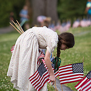 Erica Neemeyer, 11, plants flags at the Soldiers National Cemetery, during the Sesquicentennial Anniversary of the Battle of Gettysburg, Pennsylvania on Sunday, June 30, 2013.  A pivotal battle in the Civil War, over 50,000 soldiers died in the battle which spanned 3 days from July 1-3, 1863.  Later that year, President Abraham Lincoln returned to Gettysburg to deliver his now famous Gettysburg Address to dedicate the cemetery there for the Union soldiers who died in battle.  John Boal photography