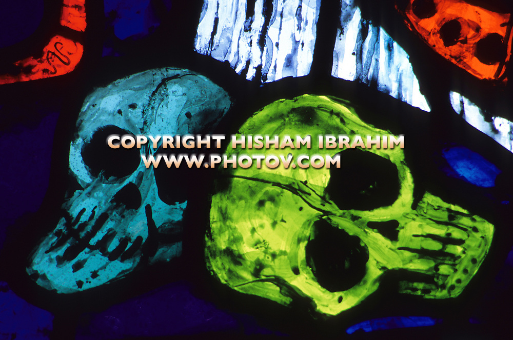 Human skulls in a stained glass window.