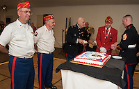 Commandant Bob Patenaude with Color Guard Harold Chamberlin and Pete Romano watch as Harold Sheffield is served the first piece of cake from Dennis Dannenfelser in traditional fashion of youngest serves oldest during the Marine Corps 241st birthday celebration at Pheasant Ridge Country Club on Saturday evening.  (Karen Bobotas/for the Laconia Daily Sun)