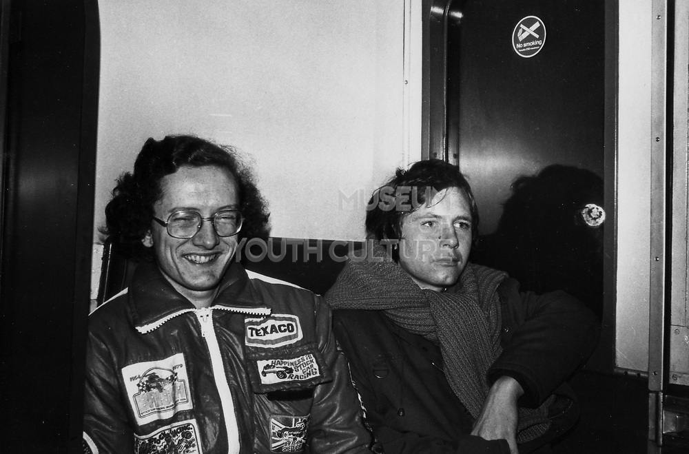 Two friends on train home after stock car meeting. London, UK, 1980s.