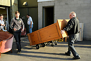 A man moves a piece of furniture on a cart while three other men go about their business outside Worth a Second Look, a part of The Working Centre in Kitchener, Ontario, Canada. The men are participants in Job Cafe, a program of The Working Centre.