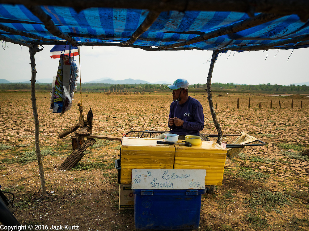 02 APRIL 2016 - NA SAK, LAMPANG, THAILAND:  A vendor waits for Thai tourists in his small shelter near Sobjant village. The village of Sobjant in Na Sak district in Lampang province was submerged when the Mae Chang Reservoir was created in the 1980s. The village was relocated to higher ground a few kilometers from its original site. The drought gripping Thailand drained the reservoir and the foundations of the Buddhist temple in the original village became visible early in 2016. Thai families come down to the original village to pray in the ruins of the temple and look at what's left of the village. This is the first time in more than 30 years that this area has not been under two meters of water.     PHOTO BY JACK KURTZ
