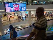 20 MAY 2015 - BANGKOK, THAILAND:   Shoppers in Siam Paragon mall in Bangkok pass a large electronic billboard. Bangkok's malls consume more electricity than some provinces. Siam Paragon, a popular high end mall in central Bangkok, consumes nearly twice as much electricity at the northern province of Mae Hong Son. Thais and foreigners alike flock to the malls in Bangkok, which are air conditioned. Most of the electricity consumed in Bangkok is generated in Laos and Myanmar. In 2013, the Bangkok Metropolitan Region consumed about 40 per cent of the Thailand's electricity, even though the BMR is only 1.5 per cent of the country's land area and about 22 per cent of its population.   PHOTO BY JACK KURTZ