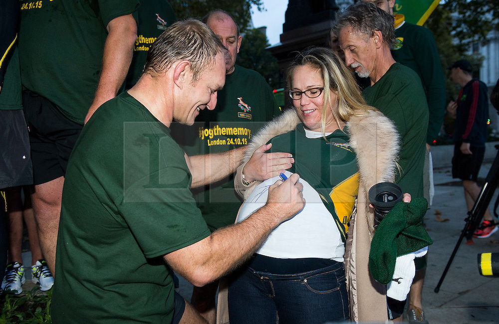 © London News Pictures. 24/10/2015. London, UK. Captain of the 1995 South African Rugby World Cup winning team, FRANCOIS PIENAAR (centre) signs a pregnant woman shirt while  taking part in an early morning, 2 mile run around westminster to mark the anniversary of in the 1995 winning team going for a morning jog. The event takes place on the morning of the Rugby World Cup semi-final between South Africa and New Zealand. Photo credit: Ben Cawthra /LNP