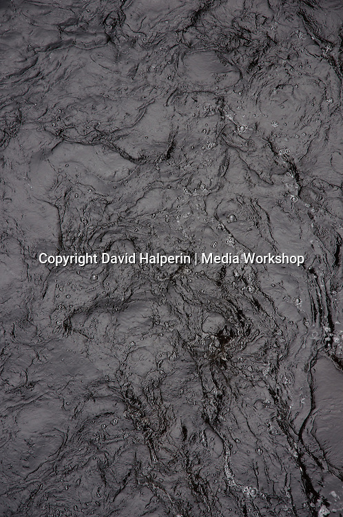 Wrinkled dark water with bubbles. Graphic pattern frozen moment.