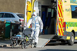 © Licensed to London News Pictures. 04/04/2020. Watford, UK. A paramedic wearing personal protective equipment outside an address in Watford prepares a stretcher. Paramedics responded to a medical incident in Watford, an ambulance an two incident response units attended   Photo credit: Peter Manning/LNP