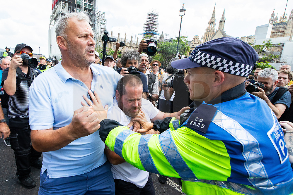 © Licensed to London News Pictures. 14/07/2018. London, UK. PICTURED: Police push back pro Trump/Robinson supporters . Supporters of EDL founder Tommy Robinson ( real name Stephen Yaxley-Lennon ) and US President Donald Trump and anti fascists clash on Westminster Bridge during a day of demonstrations and rallies in support and opposed to US President Donald Trump and jailed EDL founder Tommy Robinson . Trump is currently in Scotland and Robinson is in HMP Hull . Photo credit: Joel Goodman/LNP