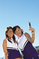 Two Cheerleaders Taking Photo of Themselves with Camera Phone