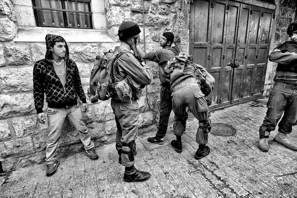 A Palestinian youth is stopped and searched by an Israeli army patrol. These searches are common and are usually considered harassment. Apr. 9, 2011. West Bank, Palestine.