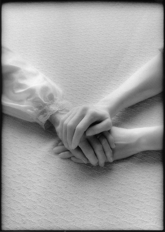 Grayscale image of clasped hands of elderly woman and caregiver on fabric background