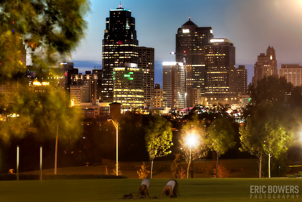 View of Kansas City Missouri downtown skyline at dusk from Hospital Hill Park with two women practicing Yoga in foreground.
