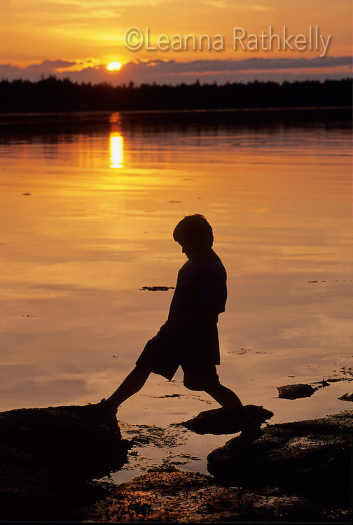 Boy, 6-8, is silouetted by sunset as he walks over rocks by ocean shore