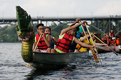 Peddlers move a Dragon Boat away from the dock. The boats offer spectators a close-up view of air-acrobatics being performed from the Strawberry Mansion Bridge, seen in the background, during the Invisible River festival on the Schuylkill River on Saturday. (Bastiaan Slabbers/for PhillyVoice)