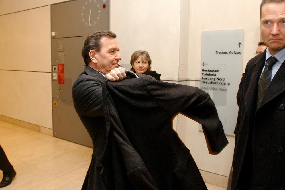 03 DEC 2002, BERLIN/GERMANY:<br /> Gerhard Schroeder, SPD, Bundeskanzler, zieht seinen Mantel an, nach einer Sitzung des SPD Gewerkschaftsrates, Deutscher Bundestag<br /> IMAGE: 20021203-02-021<br /> KEYWORDS: Gerhard Schr&ouml;der, Jacke
