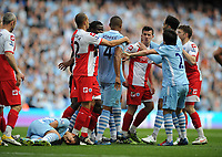 Football - Premier League - Manchester City vs. Queens Park Rangers<br /> Manchester City's Sergio Aguero falls over following a lunge from Joey Barton of Queens Park Rangers on his way off the field having been sent off at the Etihad Stadium, Manchester