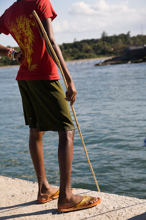 Boy with homemade bamboo fishing rod on a pier, Cojimar, Cuba