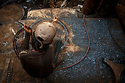 A man cuts barrel lids from a section of a steel salvaged from a supertanker. Bangladesh has a large industry built around the scrapping of ships from around the world.
