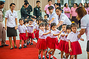 26 NOVEMBER 2012 - BANGKOK, THAILAND:   School children march into the lobby of Siriraj Hospital to pay their respects to the monarchy in Bangkok. Siriraj was the first hospital in Thailand and was founded by King Chulalongkorn in 1888. It is named after the king's 18-month old son, Prince Siriraj Kakuttaphan, who had died from dysentery a year before the opening of the hospital. It's reported to one of the best hospitals in Thailand and has been home to Bhumibol Adulyadej, the King of Thailand, since 2009, when he was hospitalized to treat several ailments. Since his hospitalization tens of thousands of people have come to pay respects and offer get well wishes. The King's 85th birthday is on Dec 5 and crowds at the hospital are growing as his birthday approaches. The King is much revered throughout Thailand and is seen as unifying force in the politically fractured country.      PHOTO BY JACK KURTZ