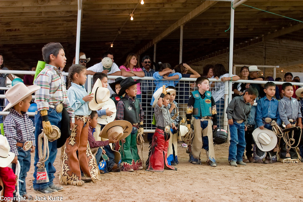 """10 SEPTEMBER 2004 - WINDOW ROCK, AZ: Navajo children enter the arena before the """"Wooly Ride"""" at the 58th annual Navajo Nation Fair in Window Rock, AZ. The Navajo Nation Fair is the largest annual event in Window Rock, the capitol of the Navajo Nation, the largest Indian reservation in the US. The Navajo Nation Fair is one of the largest Native American events in the United States and features traditional Navajo events, like fry bread making contests, pow-wows and an all Indian rodeo. The Wooly Ride, also called Mutton Busting, is a rodeo for children six years old and younger. The youngsters are set on a sheep which is then turned loose in the arena. Points are awarded for style and length of ride. Wooly Riding is extremely popular on the Navajo reservation, which has a strong cattle and sheep ranching tradition.  PHOTO BY JACK KURTZ"""