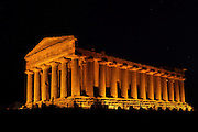 View from the side of the Temple of Concord, 5th century BC, Agrigento, Sicily, Italy,  pictured on September 11, 2009, floodlit at night. Well preserved owing to its 6th century AD conversion to a church, the Temple of Concord is a typical example of optical correction whose tapering columns create the illusion of a perfectly aligned building. Its frieze consists of alternating triglyphs and metopes, and the pediment is undecorated. The Valley of the Temples is a UNESCO World Heritage Site. Picture by Manuel Cohen.