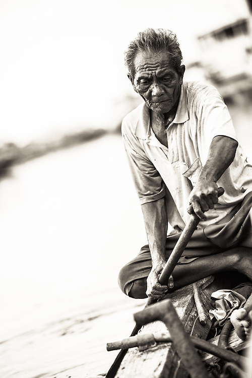 Old local man rowing to make a small living in Sunda Kelapa, the port of Jakarta