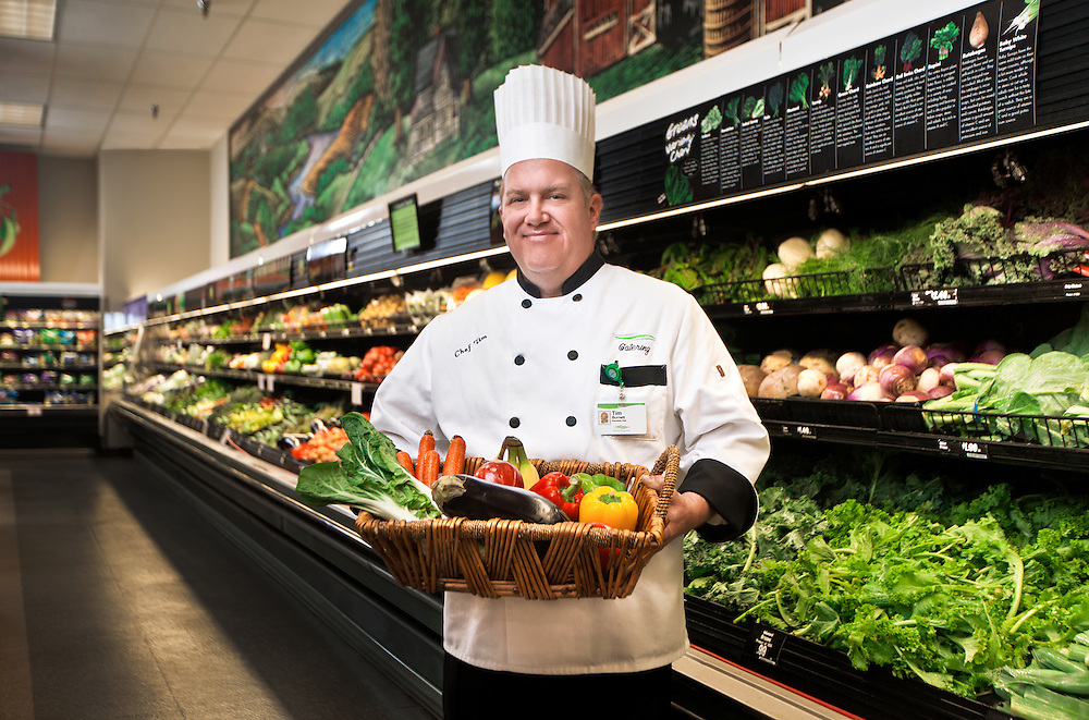 Photograph of a chef with a basket of vegetables in a grocery store produce section.