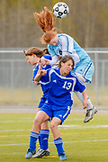 Chugiak's Alev Kelter jumps between Palmer's Krysta Theisen (13) and Arianna Cruz, back, to head the ball during the quarterfinals of the state tournament at Anchorage Football Stadium, Anchorage, Alaska, USA. Chugiak won 5-1.
