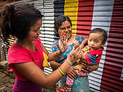 02 AUGUST 2015 - BHAKTAPUR, NEPAL:  Women with a baby in a small Internal Displaced Person (IDP) camp in Bhaktapur. Bhaktapur was badly damaged in the earthquake the hit Nepal in April 2015. The Nepal Earthquake on April 25, 2015, (also known as the Gorkha earthquake) killed more than 9,000 people and injured more than 23,000. It had a magnitude of 7.8. The epicenter was east of the district of Lamjung, and its hypocenter was at a depth of approximately 15 km (9.3 mi). It was the worst natural disaster to strike Nepal since the 1934 Nepal–Bihar earthquake. The earthquake triggered an avalanche on Mount Everest, killing at least 19. The earthquake also set off an avalanche in the Langtang valley, where 250 people were reported missing. Hundreds of thousands of people were made homeless with entire villages flattened across many districts of the country. Centuries-old buildings were destroyed at UNESCO World Heritage sites in the Kathmandu Valley, including some at the Kathmandu Durbar Square, the Patan Durbar Squar, the Bhaktapur Durbar Square, the Changu Narayan Temple and the Swayambhunath Stupa. Geophysicists and other experts had warned for decades that Nepal was vulnerable to a deadly earthquake, particularly because of its geology, urbanization, and architecture.      PHOTO BY JACK KURTZ