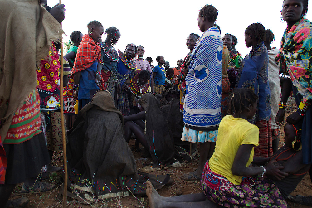 Pokot girls covered with animal skins squat on rocks after being stripped naked and washed during their circumcision rite.