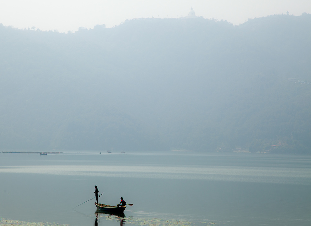 Two young men fish on the Phewa Tal in Pokhara, Nepal