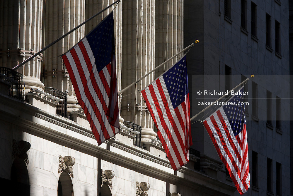 Classical pillars and American flag hanging in front of the New York Stock Exchange (NYSE) on Wall Street, Lower Manhattan,.