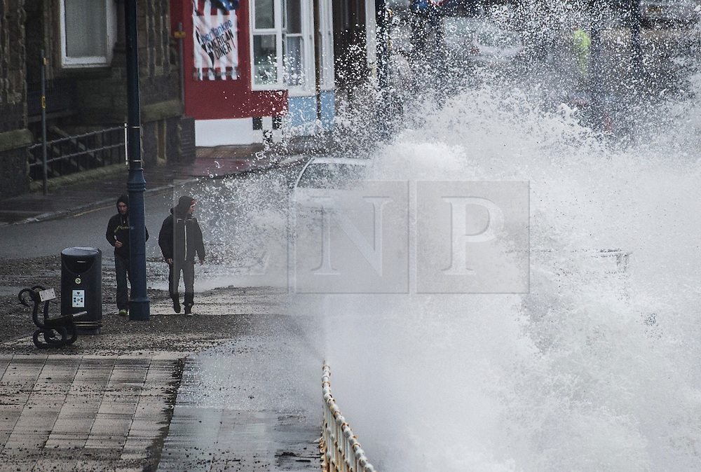 © Licensed to London News Pictures. 27/01/2016. Aberystwyth, UK.  Two men watch large waves crash against the west coast at Aberystwyth in wales at high tide. The tail end of storm Jonas continues to hit the UK, bringing torrential rain and galesPhoto credit: Keith Morris/LNP