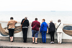 A group of friends looking over a wall at Sheringham. Norfolk UK
