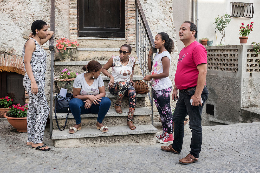Riace's three-term mayor, Domenico Lucano chatting with a group of women from Horn of Africa. In the past 18 years Riace has welcomed more than 6,000 migrants. As they arrived in Riace, an aging place with high unemployment, the mayor sensed an opportunity to revive what was quickly becoming a ghost town. He offered refugees abandoned apartments and job training.  RIACE (ITALY) 04/08/16