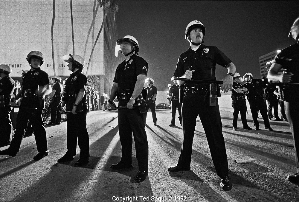 LAPD officers form a line out front of LAPD headquarters, Parker Center, on the first evening of the LA riots.<br /> <br /> Photography by Ted Soqui &copy; 1992 <br /> <br /> Los Angeles has undergone several days of rioting due to the acquittal of the LAPD officers who beat Rodney King.<br /> Hundreds of businesses were burned to the ground and over 55 people have been killed.