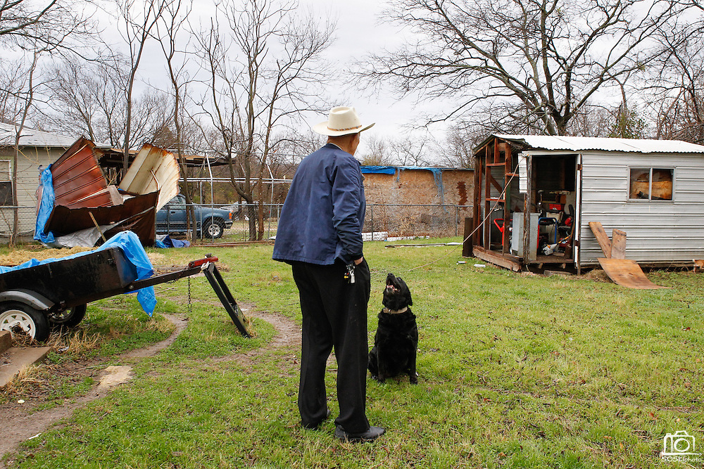Billy J. Preston, a retired World War II US Naval Amphibious Forces, looks at damage caused by a small tornado with his dog Molly at his home in Dallas, Texas, on January 29, 2013.  (Stan Olszewski/The Dallas Morning News)