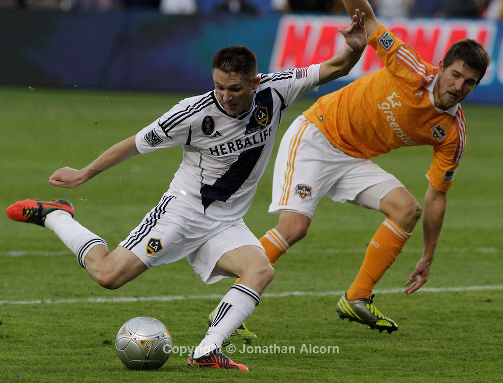 Robbie Keane shoots in front of Houston's Bobby Boswell as the Los Angeles Galaxy defeated the Houston Dynamo 3-1in the MLS Cup at the Home Depot Center in Carson, California on December 1, 2012. photo by Jonathan Alcorn