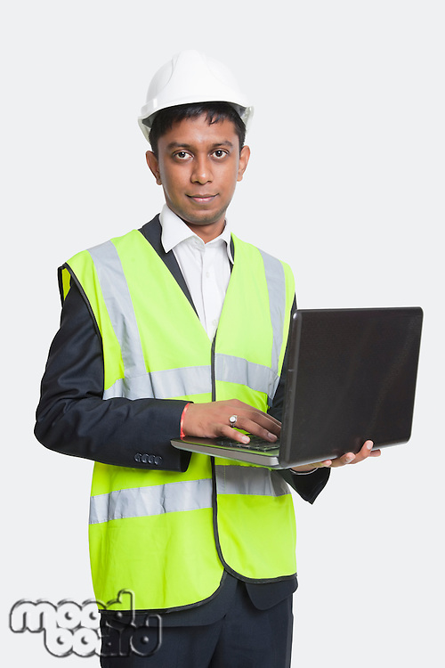 Portrait of Asian architect in reflective vest using laptop against white background