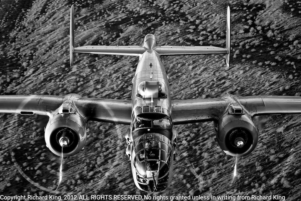 Close-up air-to-air black and white photograph of B-25 Mitchell Bomber flying over the Arizona Desert