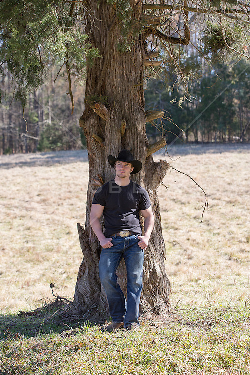 cowboy leaning against a tree in a field