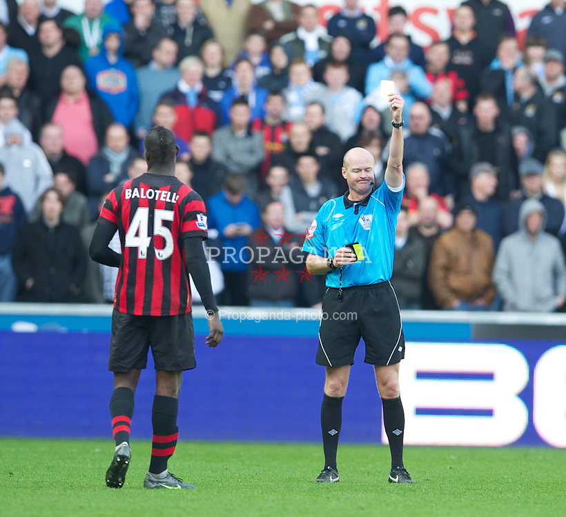 SWANSEA, WALES - Sunday, March 11, 2012: Manchester City's Mario Balotelli is shown the yellow card by referee Lee Mason against Swansea City during the Premiership match at the Liberty Stadium. (Pic by David Rawcliffe/Propaganda)