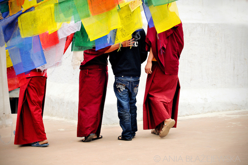 Nepal, Kathmandu. Monks walking with a boy in Boudnath Stupa.