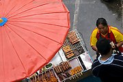 A woman is selling assorted grilled meat under a large umbrella at a street food market in Mae Sai (Sae) Thailand.